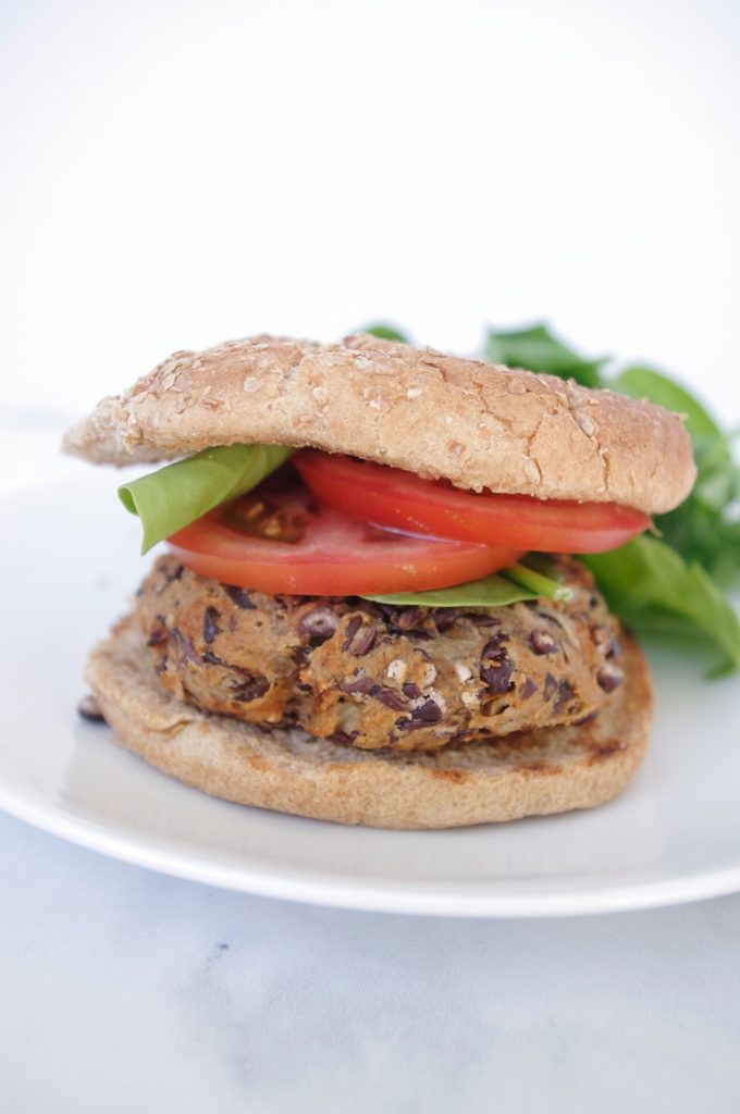 a photo of a black bean burger on a white plate, shown on a whole grain bun with tomato and lettuce