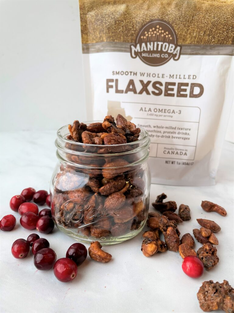 jar of candied nuts with cranberries outside of the jar and a bag of manitoba milling flaxseed behind